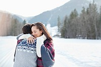 Smiling woman hugging man in snowy field (thumbnail)