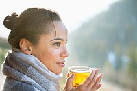 Close up of smiling woman drinking tea outdoors (thumbnail)