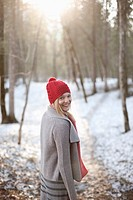 Portrait of smiling woman walking in snowy woods