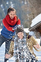 Woman breaking snowball over man's head