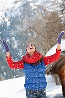 Happy woman throwing snow and looking up