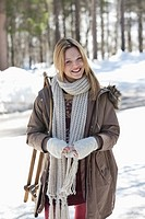 Portrait of smiling woman with sled in snowy woods