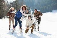 Friends throwing snowballs in field