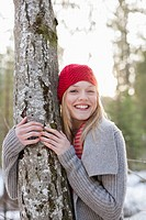 Portrait of smiling woman in red knit hat hugging tree trunk