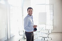 Smiling businessman holding coffee cup in conference room
