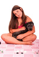 smiling brunette teenage girl in swimsuit at the beach with her shipoo dog studio setting with pink towel and little stones isolated on white backgrou...