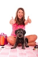 excited brunette teenage girl in swimsuit with her shipoo dog showing thumbs up gesture inviting people to go to the beach studio setting with beach a...