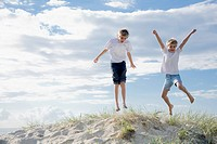 Boys jumping of a sand dune at the beach
