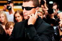 A security guard wearing dark glasses listening to his earpiece while standing in front of the paparazzi