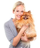 Beautiful blonde woman embracing an adorable pomeranian