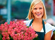 Portrait of a young florist holding a beautiful bunch of blushing pink roses