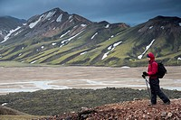 Female hiker with hiking sticks, Joekulgilskvísl river, snow_caped rhyolite mountains, Landmannalaugar, Fjallabak Nature Reserve, Highlands, Iceland, ...