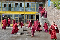 Young novice monks, students at a Buddhist monastery school, monastery building in the traditional architectural style, Tongren Monastery, Repkong, Qi...