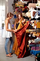Two young women choosing fabric in a showroom