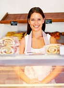Smiling young baker standing happily behind her serving counter _ portrait