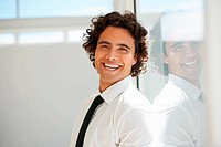 Confident young businessman smiling at you