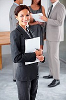 Portrait of a young executive holding a notebook and pen with her colleagues chatting in the background