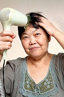 female drying her hairs with drier