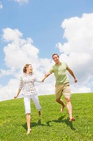 Couple running on grass