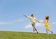 Couple running on meadow