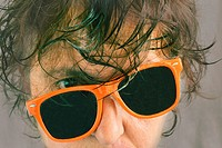portrait of woman with wet hair and tilted orange sunglasses Processed with InstaGram look with soft grey background