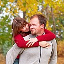 Husband Carrying His Wife On His Back In A Park In Autumn, Edmonton Alberta Canada