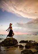 A Woman Tourist Wearing A Hat And Sarong Stands On The Beach Of A Tropical Island At Sunset, Koh Lanta Thailand
