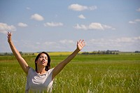 Woman Standing In A Field With Arms Raised, Three Hills Alberta Canada