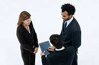 Business associates chatting while colleague uses digital tablet