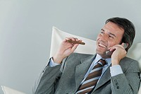 Mature businessman using cell phone and smoking cigar