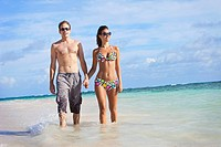 A couple walking in the shallow water along the beach holding hands, punta cana la altagracia dominican republic