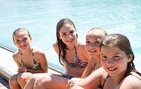 Four smiling girls in bikinis sitting at the poolside