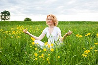 Young woman in meadow practicing yoga