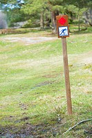 Sign with skier marking a ski track in a wintersport area during summertime