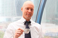 The businessman drinks coffee