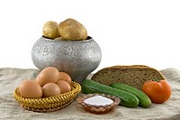 Still_life from vegetarian food. Fresh cucumbers, eggs lying in a wattled small basket, a ripe tomato, fragrant rye bread, a boiled potato in a pig_ir...