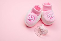 pink baby shoes and pacifier