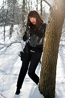 Gorgeous young woman with a rifle near the tree