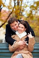 Mann umarmt lachende Frau im Park im Herbst