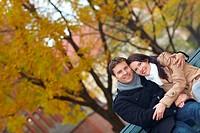 Glückliches Paar entspannt auf einer Parkbank im Herbst