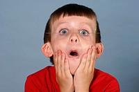 Big blue eyes, open mouth, hands on cheeks, little boy