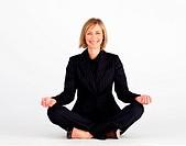 Mature businesswoman meditating on the floor