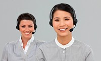Two attractive businesswomen with headset on
