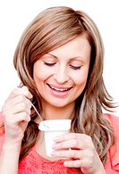 Radiant woman eating a yogurt