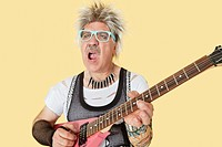 Senior male punk musician playing guitar over yellow background