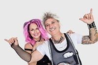 Portrait of senior punk couple over gray background