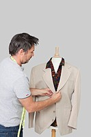Male dressmaker adjusting suit on tailor´s dummy over colored background