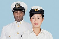 Portrait of two multi_ethnic US Navy officers over light blue background
