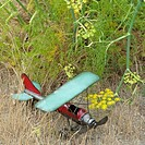 View from above. A small metal model toy aeroplane in grass. A blue wing and propeller.