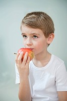 Portrait of young boy eating an apple over gray background